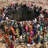 PEOPLE GATHER TO GET WATER FROM A HUGE WELL IN THE VILLAGE OFNATWARGHAD.